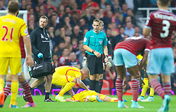 LONDON, ENGLAND - Saturday, September 20, 2014: Liverpool's Dejan Lovren is treated for a head injury against West Ham United during the Premier League match at Upton Park. (Pic by David Rawcliffe/Propaganda)