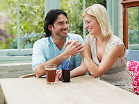 Young couple sitting at verandah table smiling