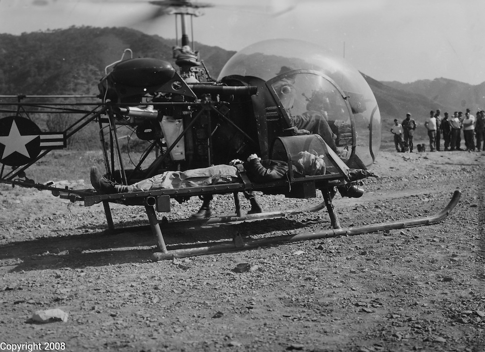 2nd Lt. Winon E. Coaley, Marine fighter pilot, who landed his F4U Corsair while wounded, is places on a helicopter at X US Corps Airstrip, Korea, for evacuation to the 8209th Mobile Army Surgical Hospital, Eighth U.S. Army. Lt. Coaley landed his plane with full load of 6 250 pound bombs. 14 May 1952