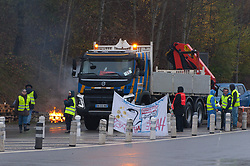 © Licensed to London News Pictures. 23/11/2018. Alby-sur-Chéran, Auvergne-Rhône-Alpes, France. Activists of the 'Gilet Jaune' national protest movement take part in 'Operation Paiement Gratuit' (free motorway) at an exit of the A41 motorway near Alby-sur-Chéran in the Auvergne-Rhône-Alpes region of France. The 'Gilet Jaune' campaign is against oppressive taxation, in particular motoring taxes on fuel etc. The name for their protest comes from the yellow Hi-Vis security waistcoat which French motorists are required to carry in vehicles by law. Photo credit: Graham M. Lawrence/LNP