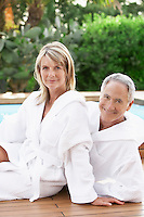 Middle-aged couple in bath robes sitting by pool portrait