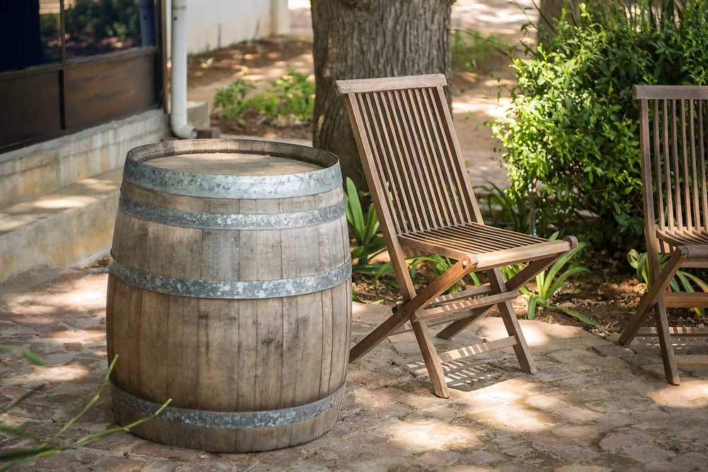 An empty wooden patio chair positioned next to barrel on patio, Cape Town, South Africa