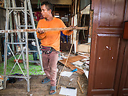 21 SEPTEMBER 2015 - BANGKOK, THAILAND: A demolition worker works at a home being torn down near Wat Kalayanamit. Fiftyfour homes around Wat Kalayanamit, a historic Buddhist temple on the Chao Phraya River in the Thonburi section of Bangkok are being razed and the residents evicted to make way for new development at the temple. The abbot of the temple said he was evicting the residents, who have lived on the temple grounds for generations, because their homes are unsafe and because he wants to improve the temple grounds. The evictions are a part of a Bangkok trend, especially along the Chao Phraya River and BTS light rail lines. Low income people are being evicted from their long time homes to make way for urban renewal.    PHOTO BY JACK KURTZ