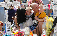 Trevor Dierecks (2nd R) kisses his son Kameron (R) with wife Rebecca (L) kissing sone Haydn (2nd L) as they knelt at a cross for Air Force Staff Sergeant Jesse Childress at a impromtu memorial near the movie theater where Childress and 11 other people where killed last Friday in Aurora, Colorado July 23, 2012. Trevor Dierecks grew up with Childress. REUTERS/Rick Wilking (UNITED STATES)