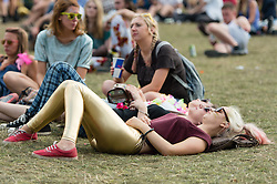 © Licensed to London News Pictures. 07/09/2014. Isle of Wight, UK. Festival goers at Bestival 2014 relax in the sunshine listening to live music on  Day 4 Sunday the final day of the festival. This weekend's headliners include Chic featuring Nile Rodgers, Foals and Outcast.   Bestival is a four-day music festival held at the Robin Hill country park on the Isle of Wight, England. It has been held annually in late summer since 2004.    Photo credit : Richard Isaac/LNP