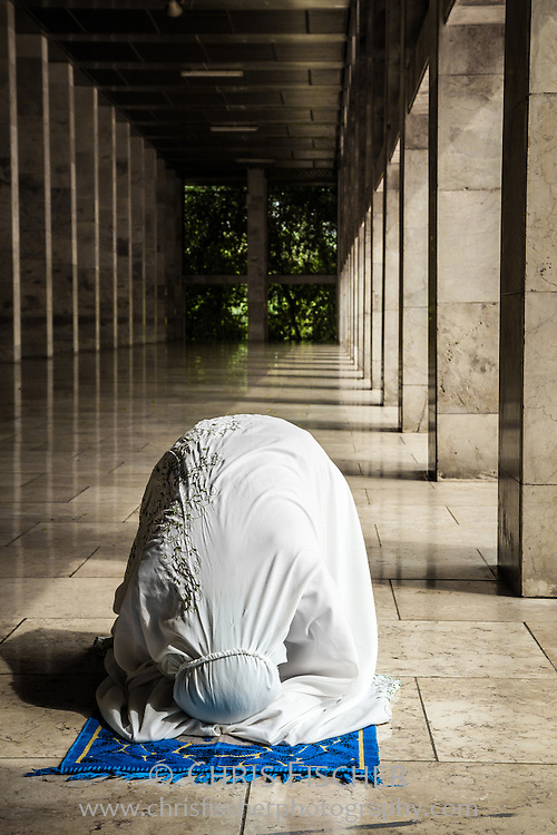 Muslim woman praying at the Istiqlal Mosque in Jakarta, Indonesia.