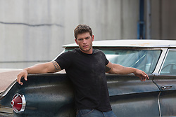 very good looking muscular auto mechanic with grease and dirt on his face leaning against a classic car