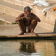A Hindu pilgrim prays before bathing in the sacred waters of Pushkar Lake. Believed to be created by the god Brahma (The Sustainer), Pushkar Lake is one of the holiest places for Hindus.