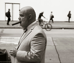 well dressed bald man smoking a cigar in New York City