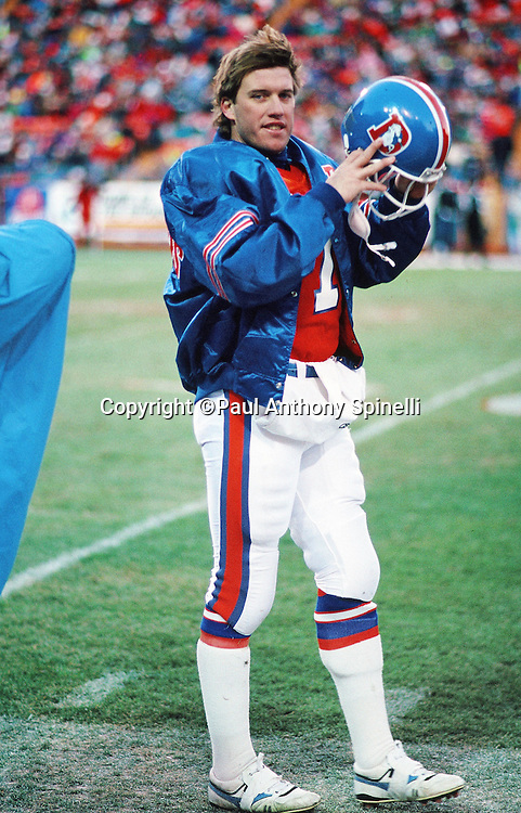 Denver Broncos quarterback John Elway (7) puts on his helmet on the sideline during the NFL football game against the Los Angeles Raiders on Dec. 2, 1990 in Denver. The Raiders won the game 23-20. (©Paul Anthony Spinelli)