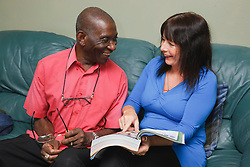 Elderly black man with white woman carer at home looking at catalogue