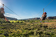 Two women zip side by side while zip lining in the Snake River Canyon with Zip the Snake in Twin Falls, Idaho.