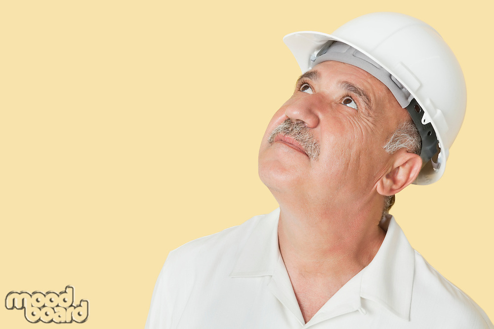 Senior construction worker with hardhat looking up over yellow background