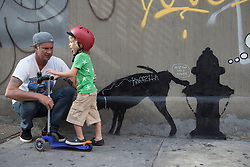 "Banksy graffiti art in New York City, October 3, 2013. Red Hot Chili Peppers Drummer Chad Smith stands next to Banksy's new piece in New York City. The piece, titled ""Midtown"", is located on 24th St. and 6th Ave. Banksy has come to New York City and ""will be attempting to host an entire show on the streets of New York,"" according to his website. His show is titled ""Better Out Than In"". Photo by Michael Graae / i-Images."