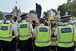 """© Licensed to London News Pictures. 21/06/2017. London, UK. A visible police presence is evident as protesters stage a demonstration in Parliament Square after the Queen's Speech on a so called """"Day of Rage"""".   Many were demanding justice for the victims of the Grenfell Tower fire whilst others were supporting Jeremy Corbyn and the Labour party.. Photo credit : Stephen Chung/LNP"""