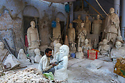 A stone mason/sculptor works on images of famous people, Varanasi