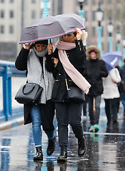 © Licensed to London News Pictures. 08/02/2019. London, UK.  Two women hold onto their umbrella as they walk in wet and windy weather on Tower Bridge. Storm Erik is the first named storm of 2019 with gale force winds and wet weather affecting most of the UK today. Photo credit: Vickie Flores/LNP