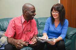 Elderly black man with white woman carer at home looking at post