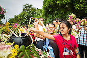 "22 JULY 2013 - PHRA PHUTTHABAT, THAILAND: People put flowers on a truck carrying a statue of the Buddha during the Tak Bat Dok Mai at Wat Phra Phutthabat in Saraburi province of Thailand, Monday, July 22. Wat Phra Phutthabat is famous for the way it marks the beginning of Vassa, the three-month annual retreat observed by Theravada monks and nuns. The temple is highly revered in Thailand because it houses a footstep of the Buddha. On the first day of Vassa (or Buddhist Lent) people come to the temple to ""make merit"" and present the monks there with dancing lady ginger flowers, which only bloom in the weeks leading up Vassa. They also present monks with candles and wash their feet. During Vassa, monks and nuns remain inside monasteries and temple grounds, devoting their time to intensive meditation and study. Laypeople support the monastic sangha by bringing food, candles and other offerings to temples. Laypeople also often observe Vassa by giving up something, such as smoking or eating meat. For this reason, westerners sometimes call Vassa the ""Buddhist Lent.""        PHOTO BY JACK KURTZ"