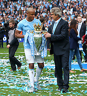 Manuel Pellegrini and Vincent Kompany of Manchester City carry the Barclays Premier League trophy after the presentation at the Etihad Stadium, Manchester<br /> Picture by John Rainford/Focus Images Ltd +44 7506 538356<br /> 11/05/2014