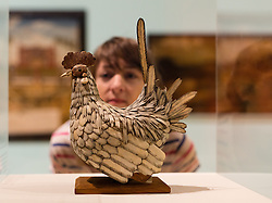 © Licensed to London News Pictures. 08/06/2014. London, UK. A woman looks at a bone cockerel at the British Folk Art exhibition at Tate Britain in Millbank, London on 8th June 2014. The British Folk Art exhibition at Tate Britain opens on 10th June 2014 and runs until 31st August 2014. Photo credit : Vickie Flores/LNP