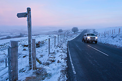 © Licensed to London News Pictures. 31/01/2019. Builth Wells, Powys, Wales, UK. A motorist drives along the B4520 (Brecon road) through a bitterly cold wintry landscape at dawn on the Mynydd Epynt range near Builth Wells in Powys, Wales, UK where temperatures dropped dramatically overnight to minus seven degrees centigrade (temperature certified by photographer) <br />  credit: Graham M. Lawrence/LNP