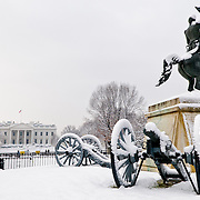 A statue of President Andrew Jackson, surrounded by cannons, in Lafayette Park covered in fresh snow. In the background, at left of the frame, is the White House. With this statue in the center of the park, it used to be known as Jackson Park.