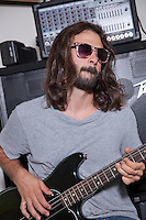 Young man wearing sunglasses practicing with guitar