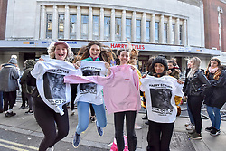© Licensed to London News Pictures. 29/10/2017. London, UK.  Fans of singer, Harry Styles, pose to show of their 'merch' (merchandise) outside the Hammersmith Eventim Apollo in West London ahead of his first UK solo shows taking place on 29 and 30 October.  Many fans, eager to secure a space as close to the stage as possible have queued overnight, sleeping on the pavement in their sleeping bags or under duvets.  Fans immediately outside the entrance to the venue (pictured) will be seeing the singer perform on the 29 October, whilst those under the nearby Hammersmith flyover have arrived a day early with tickets for 30 October.  Photo credit: Stephen Chung/LNP