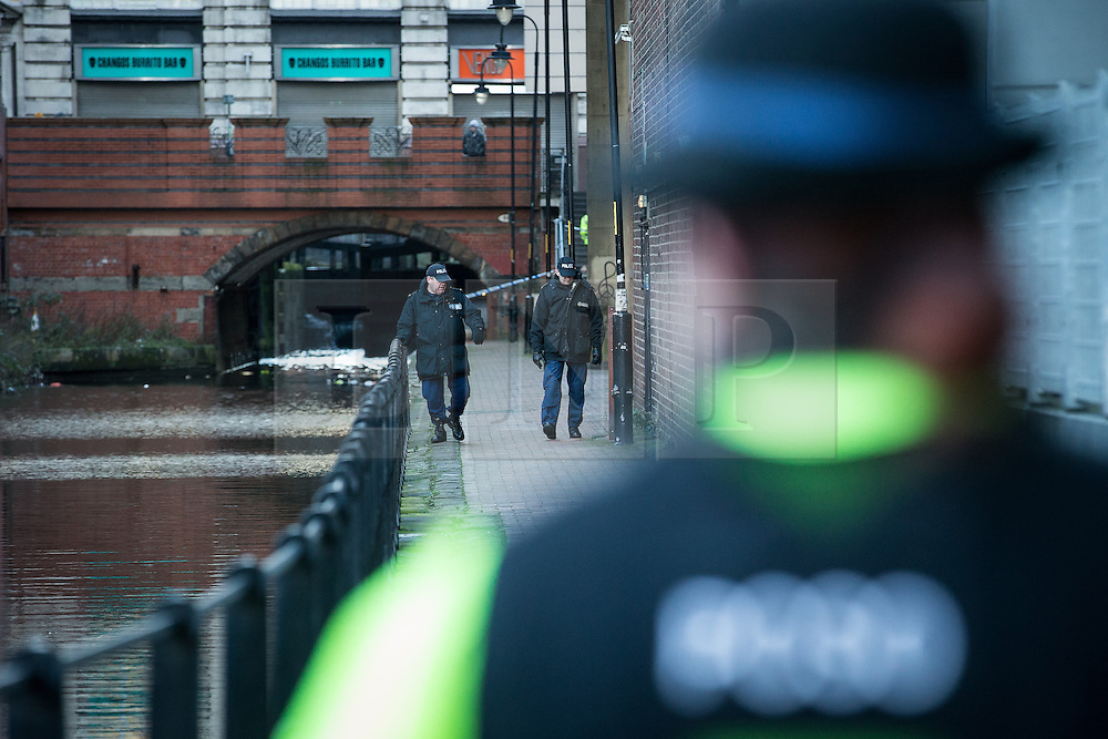 © Licensed to London News Pictures . 29/12/2013 . Manchester , UK . A PCSO stands behind police tape adjacent to the River Medlock off Oxford Road in Manchester City Centre as two officers search the footpath. The search for 17 year old Adam Pickup from Stockport , who was last seen in the early hours of Saturday 28th December in Manchester City Centre following a night out with friends as , this evening (Sunday 29th December 2013), Greater Manchester Police say they have arrested two men in connection with the teenager's disappearance . Photo credit : Joel Goodman/LNP