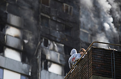 © Licensed to London News Pictures. 14/06/2017. London, UK. A couple look from their balcony directly below the building Grenfell Tower at the Lancaster West Estate -  scene of a huge fire in west London. The blaze engulfed the 27-storey building with 200 firefighters attending the scene. A number of fatalities have been reported. Photo credit: Peter Macdiarmid/LNP
