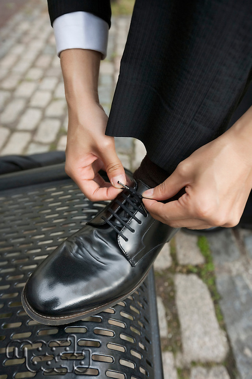 Cropped image of businessman tying his shoe outside