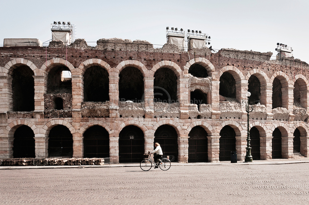 A lone cyclist travels by the  Roman amphitheatre in Verona, Italy.