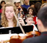 Rilla Cornelius, 22 months of Bellbrook watches holiday music from Centerville High School Orchestra members Margaret Otto (left) and Justin Lun at the WashingtonCenterville Public Library in Centerville, Monday, December 5, 2011.