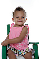 20 July 2008: Adopted little girl a 14 month old bi-racial toddler named Mason Mangus in the studio on a white background sitting happy in a green chair and pink top.