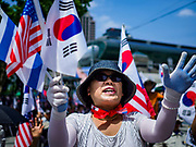 16 JUNE 2018 - SEOUL, SOUTH KOREA: A South Korean woman holding South Korean and American flags cheers during a protest against South Korean President Moon Jae-in. Most of the protesters support jailed former President Park Geun-hye. President Moon Jae-in was elected in 2017 after Park was impeached, tried and convicted on corruption charges. The protesters allege that Moon is too soft on North Korea and can't be trusted to negotiate with North Korean leader Kim Jong-un. They support US President Donald Trump's efforts to negotiate with the North Korean strongman.   PHOTO BY JACK KURTZ