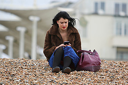 © Licensed to London News Pictures. 26/10/2014. Brighton, UK. A woman relaxes on the beach on Sunday morning October 26th. A cloudy day with possibility of some localised showers. The temperatures are expected to reach 15C in Brighton and the South Coast. Photo credit : Hugo Michiels/LNP