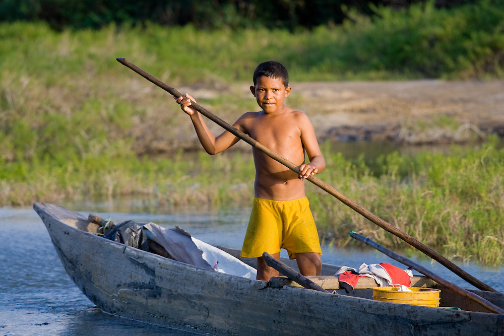A boy paddles a canoe near Baranquilla, Colombia