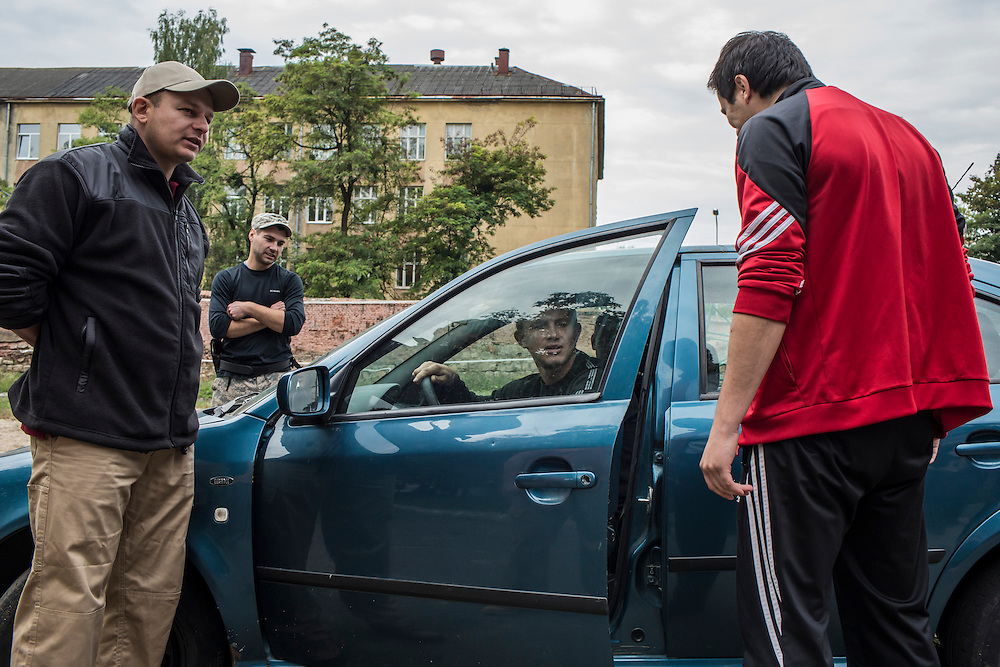 LVIV, UKRAINE - OCTOBER 5, 2015: Instructor Yurii Shevchyk, left, teaches recruits how to apprehend a suspect during a traffic stop during tactical training for new patrol police officers in Lviv, Ukraine. In an effort to reform the notoriously corrupt Ukrainian police force, an entirely new force has been established in several cities, including Kiev and Lviv, with a primary focus on patrolling the streets. CREDIT: Brendan Hoffman for The New York Times