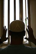 A Muslim prisoner praying in his cell. HMP Wandsworth, London, United Kingdom