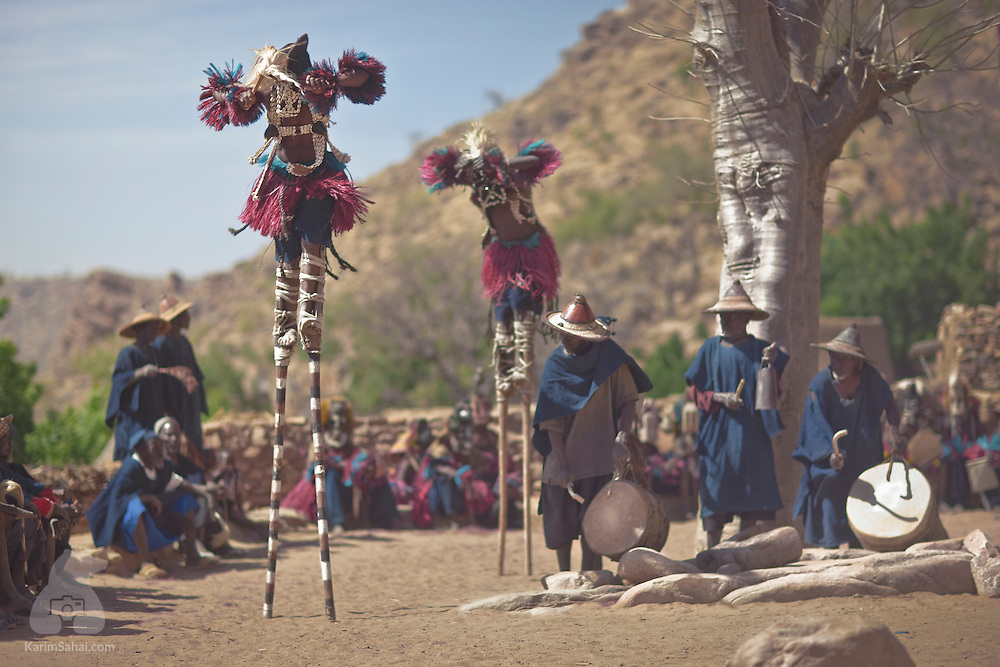 Mask-wearing dancers perfom a ritual dance on stilts in the Dogon village of Tireli, Mali.