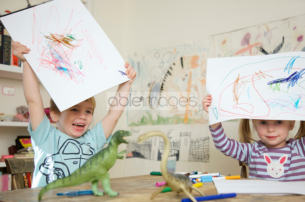 Close up of a boy and girl holding drawings above their heads