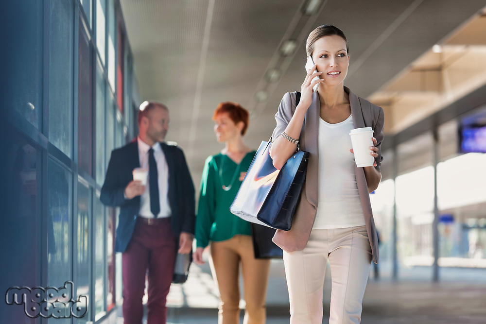 Portrait of young attractive businesswoman talking on smartphone and holding cup of coffee while walking against colleague