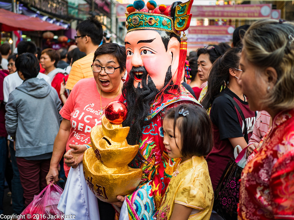 "08 FEBRUARY 2016 - BANGKOK, THAILAND:  People pose for photos with a Taoist deity during the Chinese New Year parade in Bangkok's Chinatown district during the celebration of the Lunar New Year. Chinese New Year is also called Lunar New Year or Tet (in Vietnamese communities). This year is the ""Year of the Monkey."" Thailand has the largest overseas Chinese population in the world; about 14 percent of Thais are of Chinese ancestry and some Chinese holidays, especially Chinese New Year, are widely celebrated in Thailand.      PHOTO BY JACK KURTZ"
