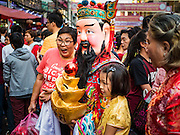 """08 FEBRUARY 2016 - BANGKOK, THAILAND:  People pose for photos with a Taoist deity during the Chinese New Year parade in Bangkok's Chinatown district during the celebration of the Lunar New Year. Chinese New Year is also called Lunar New Year or Tet (in Vietnamese communities). This year is the """"Year of the Monkey."""" Thailand has the largest overseas Chinese population in the world; about 14 percent of Thais are of Chinese ancestry and some Chinese holidays, especially Chinese New Year, are widely celebrated in Thailand.      PHOTO BY JACK KURTZ"""