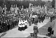 Funeral of Eamon DeValera.   (J72)..1975..02.09.1975..09.02.1975..2nd September 1975..Today saw the funeral of Eamon DeValera. He was laid to rest beside his wife Sinead in Glasnevin Cemetery,Dublin. Dignitries from all around the world attended at the funeral..The Tricolour draped coffin of Eamon DeValera is ceremonially carried to the graveside by military personnel.Picture shows the mourners taking up every available vantage point.