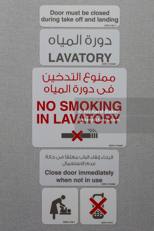 Detail of multi-language toilet signage in a Qatar Airways Airbus A350-1000 at the Farnborough Airshow, on 18th July 2018, in Farnborough, England.