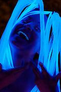 A portrait of a laughing woman wearing a glowing deadlock headpiece.Black light