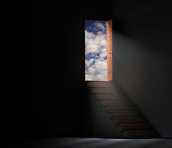 Stairway from a dark basement leading to the outside with clouds and blue sky