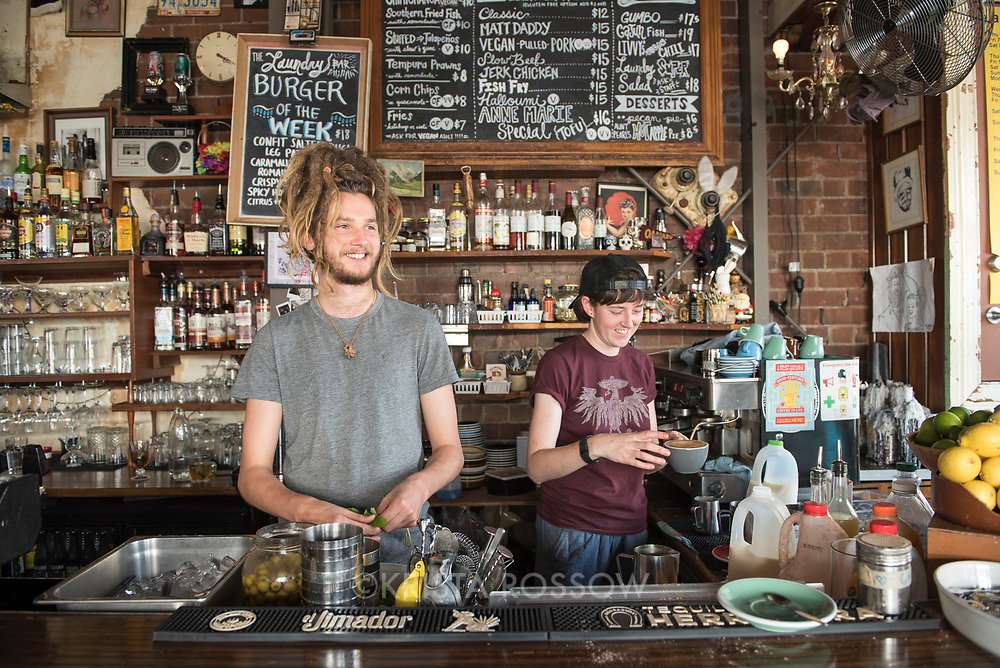 Images of female (maroon t-shirt) and male (dreadlocks) bartenders are model released. The Laundry Bar and Restaurant serves Southern inspired soul food and cocktails on Cuba Street in Te Aro, Wellington. Address: 234 Cuba St, Te Aro, Wellington 6011, New Zealand